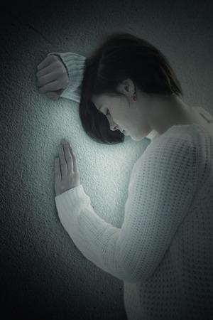 wistfulness: Sad pretty brunette leaning against wall against grey wall