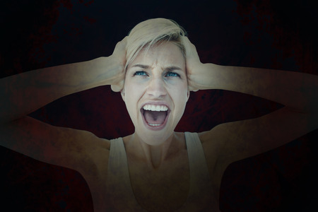 outraged: Angry blonde screaming and holding her head  against dark background