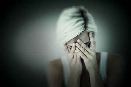 desolación: Sad blonde woman crying with head on hands  against grey vignette