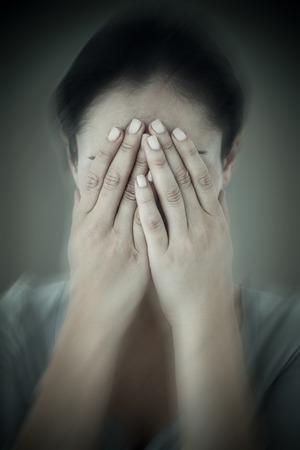 desolaci�n: Sad woman hiding her face against grey background with vignette Foto de archivo