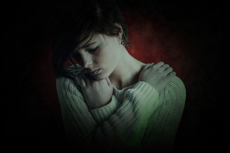 wistfulness: Sad pretty brunette thinking with arms crossed against dark background Stock Photo