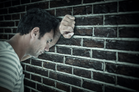 dreariness: Upset man leaning on white background against red brick wall