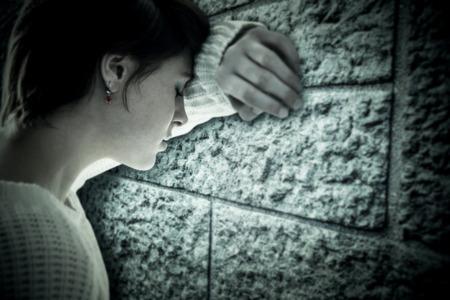 persona triste: Triste bastante morena apoyándose contra la pared contra la pared de ladrillo gris