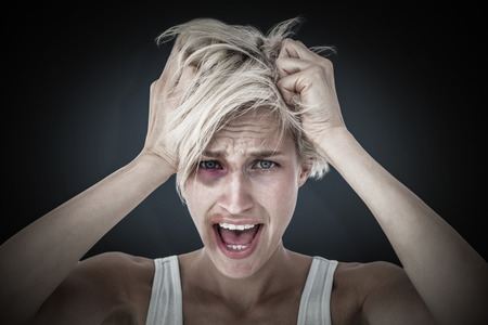 apprehensive: Stressed woman screaming and holding her head  against blue background with vignette Stock Photo