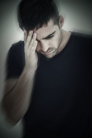 man sad: Sad man holding his forehead with his hand against grey vignette Stock Photo