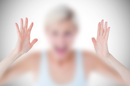 angry blonde: Angry blonde screaming with hands up  against white background with vignette