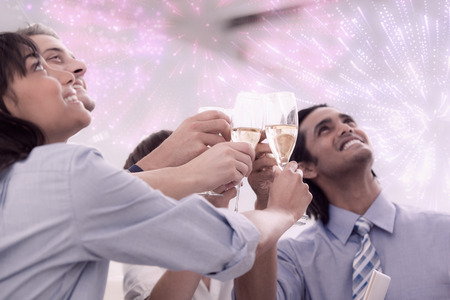 self assured: Cheerful business team toasting with Champagne against colourful fireworks exploding on black background