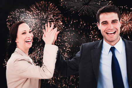workmates: Cheerful workmates doing high five against colourful fireworks exploding on black background