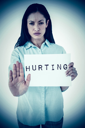 hurting: Woman showing card and saying stop against hurting