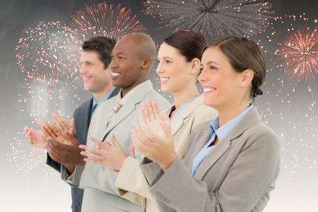 upright row: Side view of clapping sales team standing together against colourful fireworks exploding on black background