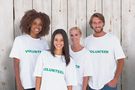 selfless: Happy group of volunteers against wooden background
