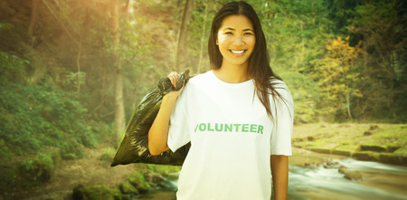 charity work: Team of volunteers picking up litter in park against rapids flowing along lush forest Stock Photo