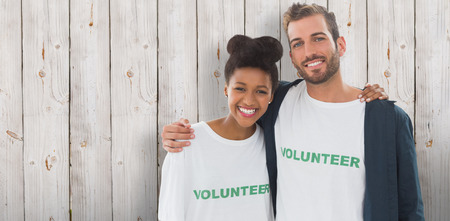 arms around: Portrait of two young volunteers with arms around against wooden background Stock Photo