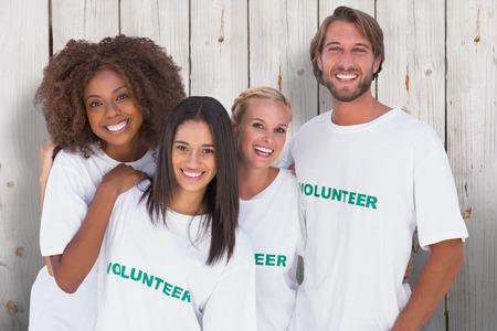 volunteer: Smiling group of volunteers against wooden background Stock Photo