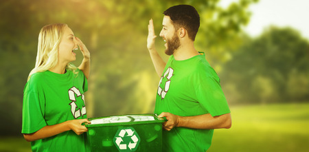 Smiling volunteer doing high five while holding container  against trees and meadow Stock Photo