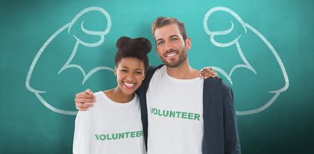arms around: Portrait of two young volunteers with arms around against green chalkboard Stock Photo