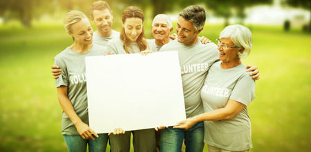 Happy volunteer family holding a blank  against park