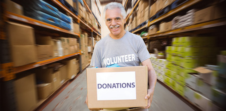 active adult community: Happy volunteer senior holding donation box against worker with trolley of boxes Stock Photo