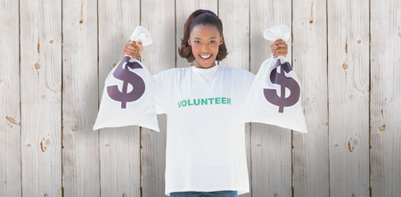 selfless: Smiling volunteer woman holding money bags  against wooden background