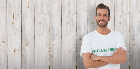 Portrait of a happy male volunteer with hands crossed against wooden background