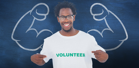 selfless: Handsome man pointing to his volunteer tshirt against blue chalkboard