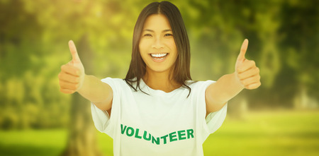 Woman wearing volunteer tshirt giving thumbs up against trees and meadow