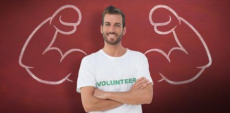 mani incrociate: Ritratto di un volontario maschio felice con le mani incrociate contro scrivania
