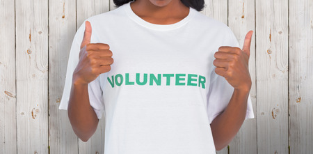 selfless: Woman wearing volunteer tshirt and giving thumbs up against wooden background Stock Photo