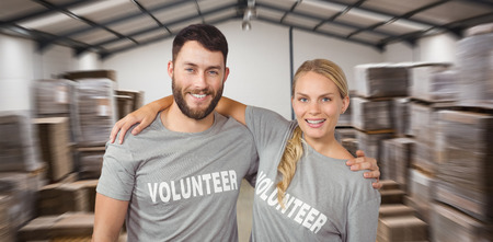arms around: Portrait of colleagues with arms around standing  against many stack of cardboard boxes Stock Photo