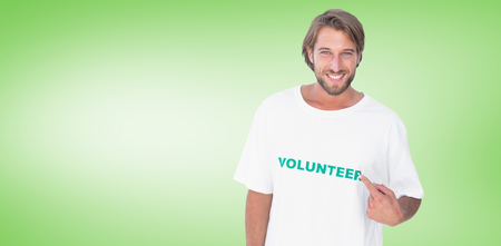 volunteer point: Smiling man pointing to his volunteer tshirt against green vignette