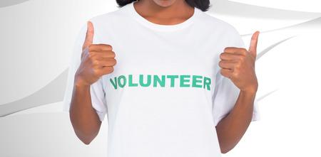 volunteer: Woman wearing volunteer tshirt and giving thumbs up against white wave design