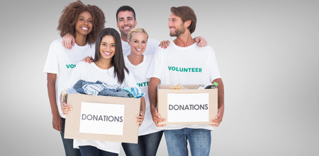 colour box: Happy group of volunteers holding clothes donation boxes against grey vignette