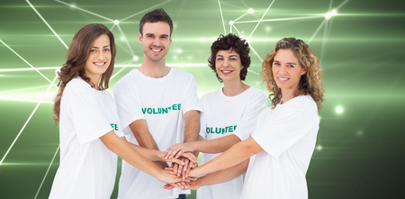 piling: Smiling volunteer group piling up their hands against glowing geometric design Stock Photo