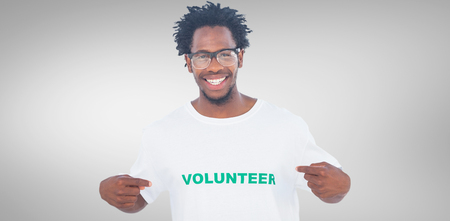 selfless: Handsome man pointing to his volunteer tshirt against grey vignette Stock Photo