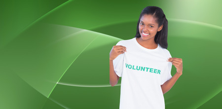 against abstract: Young woman wearing volunteer tshirt and pointing to it against abstract green design Stock Photo