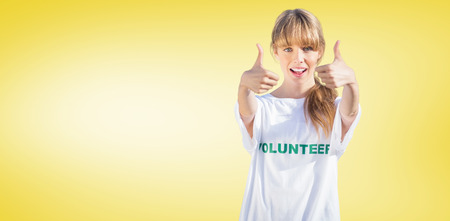 volunteering: Natural blonde wearing a volunteering t shirt giving thumbs up against yellow vignette