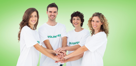 piling: Smiling volunteer group piling up their hands against green vignette