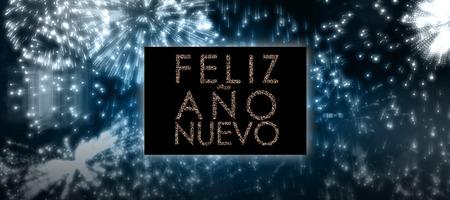 ano: Glittering feliz ano nuevo against colourful fireworks exploding on black background