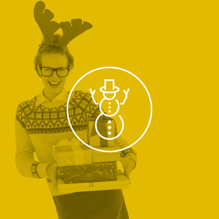 geeky: Happy geeky hipster holding presents  against snowman Stock Photo