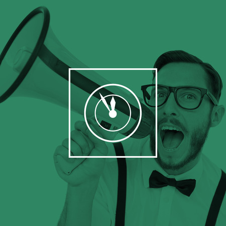 against the clock: Geeky businessman shouting through megaphone against clock Stock Photo