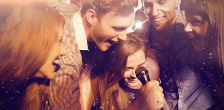 gente cantando: gran �xito en contra de amigos felices juntos cantando karaoke Foto de archivo
