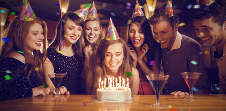 Flying colours against friends celebrating a birthday together Stock Photo
