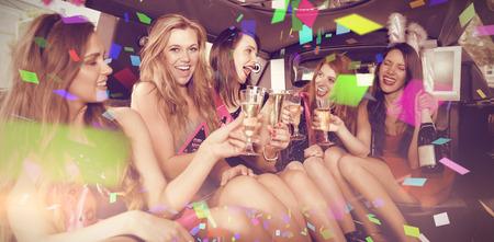 Bravúrral ellen boldog barátok pezsgőt iszik a limuzinban Stock fotó