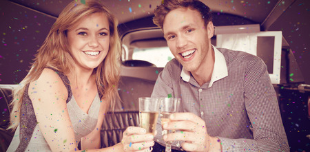 hedonistic: Flying colours against happy couple drinking champagne in limousine Stock Photo