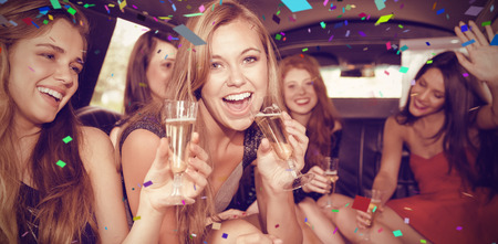 limo: Flying colours against happy friends drinking champagne in limousine Stock Photo