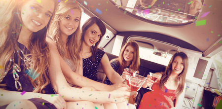 limo: Flying colours against happy friends drinking cocktails in limousine Stock Photo