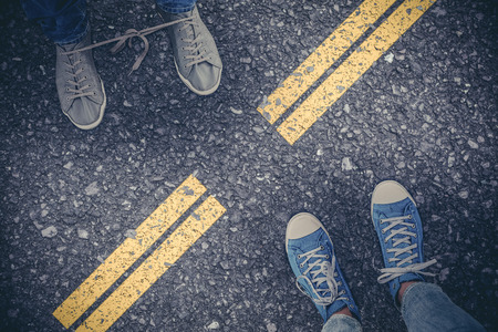 tied together: Low section of man with shoelaces tied together  against road