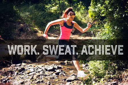 get a workout: Motivational new years message against sporty young woman leaping over a stream Stock Photo