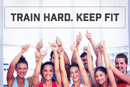 thumbs up: Motivational new years message against fit people gesturing thumbs up in exercise room Stock Photo
