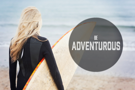 wet suit: Motivational new years message against rear view of woman in wet suit holding surfboard at beach Stock Photo